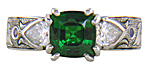 A cushion-cut Tsavorite garnet set in a beautifully hand crafted and engraved platinum ring.